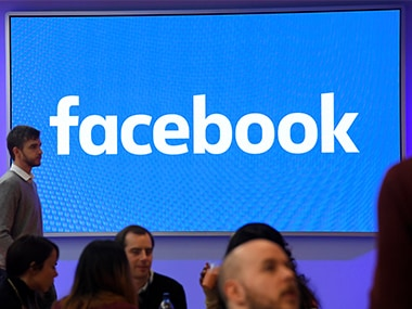 People stand in front of a logo at Facebook's headquarters in London. Image: Reuters