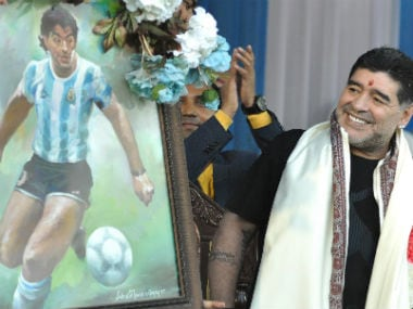 Argentine footballer Diego Maradona looks at his portrait during a visit to Kolkata. AFP