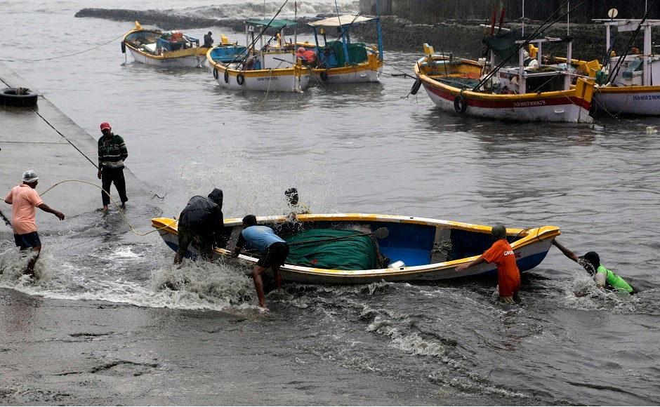 Fishermen pull their boat during high tide in the Arabian Sea in Mumbai. Mumbai police put up barricades near Dadar Chowpatty and Juhu Chowpatty to prevent people from going near the beaches. AP