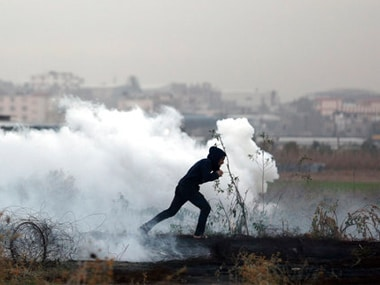 A Palestinian protester runs for cover from teargas fired by Israeli troops during clashes on the Israeli border with Gaza. AP