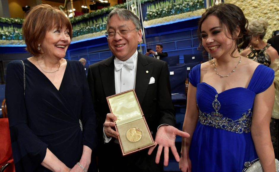 Kazuo Ishiguro poses with his Nobel Prize in literature, flanked by his wife Lorna MacDougall and his daughter Naomi Ishiguro after the Nobel Award Ceremony. Reuters