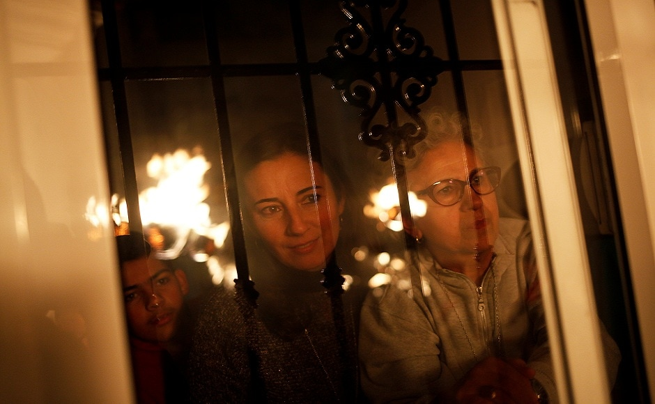 People watch from their house as villagers hold torches to represent light and vision during the Divina Pastora procession, as part of a festival to honour the Virgin of Los Rondeles, on the eve of St. Lucia's Day, in Casarabonela, near Malaga, southern Spain. REUTERS