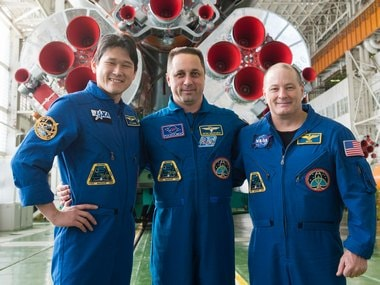 In the Integration Facility at the Baikonur Cosmodrome in Kazakhstan, crewmembers pose for pictures in front of the first stage of the Soyuz booster rocket. Image: Gagarin Cosmonaut Training Center/ NASA