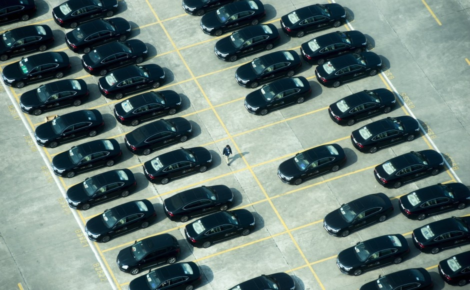 """A person walks amongst escort vehicles parked outside the Fortune Global Forum in Guangzhou, China. Speaking to reporters on Tuesday, Trudeau reiterated that a deal with China was not an """"overnight process"""". AP"""