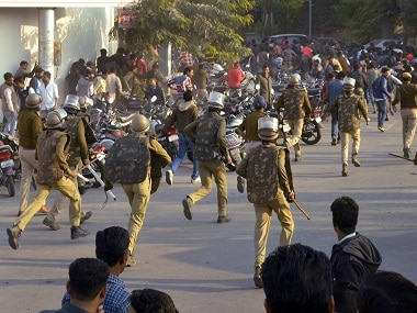 Police chasing activists during the protest rally. PTI