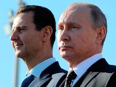 Russian President Vladimir Putin and Syrian President Bashar Assad watch the troops marching at the Hemeimeem air base in Syria. AP