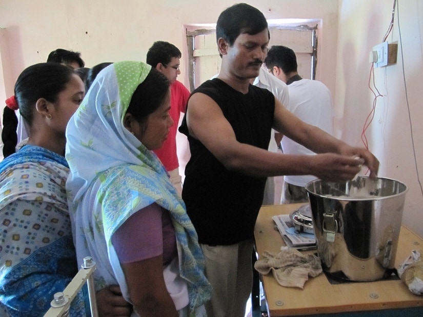 Muruganantham demonstrates how his machine works to the women who will then manufacture the low-cost sanitary napkins on it