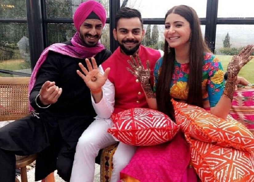 Virat Kohli and Anushka Sharma with a guest at their mehendi. Image from Twitter.
