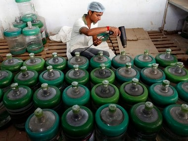 A worker seals bottles of drinking water inside a bottled water industry on the outskirts of Ahmedabad