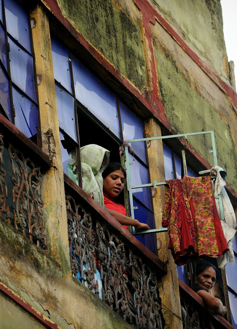 Indian sex workers watch as visiting sex workers march in the biggest red light district of the country, Sonagachi during a rally as part of the Sex Workers' Freedom Festival in Kolkata on July 24, 2012. Sex workers and social actiists from 42 countries are congregrating in this city to participate in the week long festival organised to protest against the US government's travel restrictions on sex workers wanting to attend an international AIDS conference in Washington. AFP PHOTO/Dibyangshu SARKAR / AFP PHOTO / DIBYANGSHU SARKAR