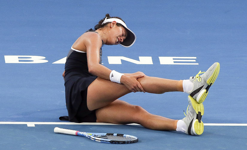 Garbine Muguruza of Spain grabs her leg in pain before retiring from her second round match against Aleksandra Krunic of Serbia at the Brisbane International tennis tournament at the Pat Rafter Arena in Brisbane on January 2, 2018. Muguruza suffered a fitness scare ahead of this month's Australian Open when she was forced to retire from the Brisbane International on January 2 with severe cramping. / AFP PHOTO / Franca TIGANI / --IMAGE RESTRICTED TO EDITORIAL USE - STRICTLY NO COMMERCIAL USE--
