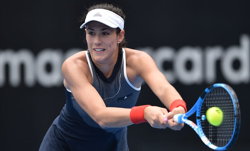 Garbiñe Muguruza of Spain hits a return to Kiki Bertens of the Netherlands in their women's singles second round match at the Sydney International tennis tournament in Sydney on January 10, 2018. / AFP PHOTO / PETER PARKS / -- IMAGE RESTRICTED TO EDITORIAL USE - STRICTLY NO COMMERCIAL USE --
