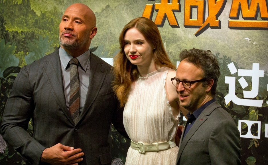 From left, Dwayne Johnson, Karen Gillan, and Jake Kasdan pose for photos on the red carpet. AP/Mark Schiefelbein