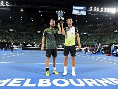 Austria's Oliver Marach, left, and Croatia's Mate Pavic hold their trophy aloft after winning the men's doubles final against Colombia's Juan Sebastian Cabal and Robert Farah at the Australian Open tennis championships in Melbourne, Australia, early Sunday, Jan. 28, 2018. (AP Photo/Andy Brownbill)