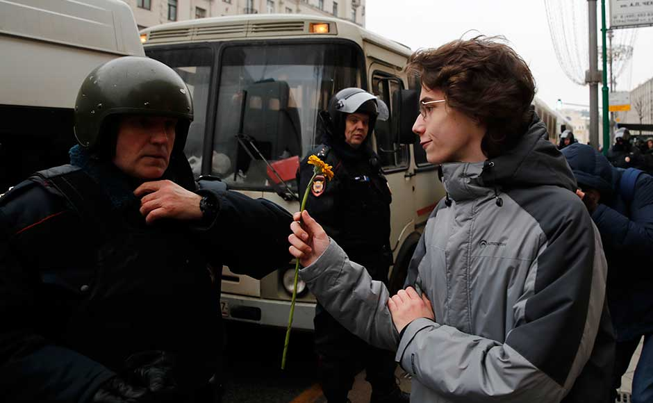 Last year, he called for two demonstrations which attracted people throughout the country, undermining critics' claims that he appeals only to a narrow segment of prosperous urbanites. A protester offers a flower to a policeman during a rally in Moscow. AP