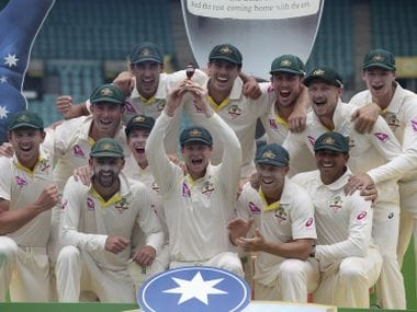 Steve Smith, centre, holds up the replica of the Ashes urn as Australian players celebrate their win over England. AP