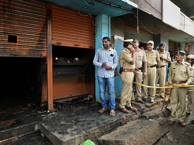 Police officers stand guard at the site after a fire broke out at a bar-cum-restaurant in Bengaluru. PTI