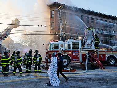Firefighters work to contain a fire in the Bronx section of New York on Tuesday. AP