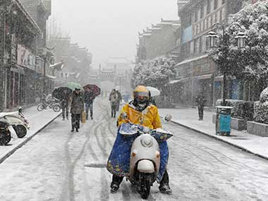 People are seen amid snow in Xiangyang, Hubei province, China. Reuters