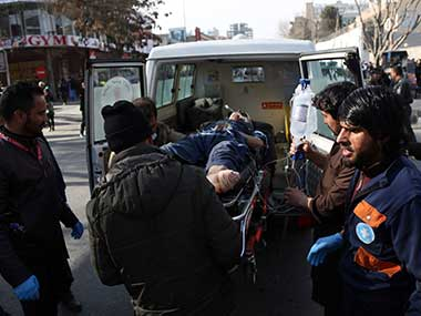People help carry an injured man to the hospital following a suicide attack in Kabul, Afghanistan. AP