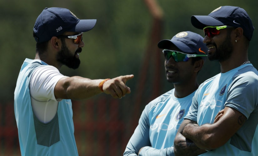 Virat Kohli chats with Wriddhiman Saha and Shikhar Dhawan, the two players likely to be dropped by India for the second Test. AP