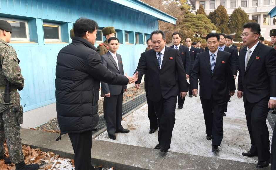 Head of North Korean delegation Ri Son Gwon, Chairman of the Committee for the Peaceful Reunification of the Country (CPRC) of DPRK, is greeted by a South Korean official as he crosses a concrete border to attend their meeting at the truce village of Panmunjom in the demilitarised zone separating the two Koreas. Reuters