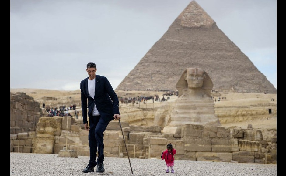 World's tallest man Sultan Kosen from Turkey (left) and world's shortest woman Jyoti Amge from India pose together in Egypt with the towering Pyramids of Giza and the Sphinx at the background. AFP