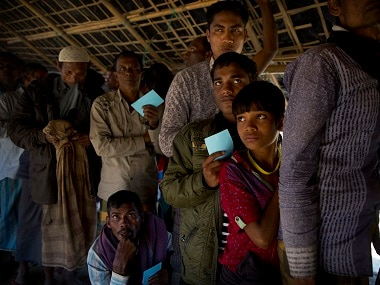 Rohingya refugees wait in a queue to receive daily items at a distribution center near Cox's Bazar. AP