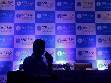 A man walks past a podium set up at the venue of a news conference to announce the launch of Initial Public Offering by SBI Life Insurance Co in Mumbai
