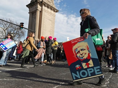 A women holds a poster depicting President Donald Trump during a Women's March in Chicago on Saturday. AP