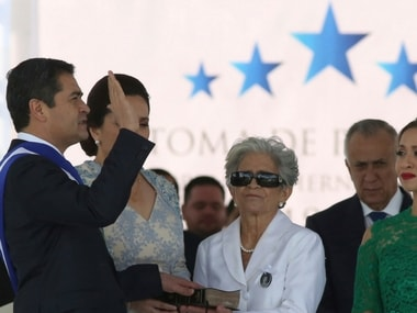 Honduran President Juan Orlando Hernandez takes the oath of office with his hand placed on a Bible held by his mother Elvira Alvarado, accompanied by his wife Ana Garcia, second left, and their daughter Ivonne Hernandez, right, at the National Stadium in Tegucigalpa, Honduras, Saturday, Jan. 27, 2018. AP