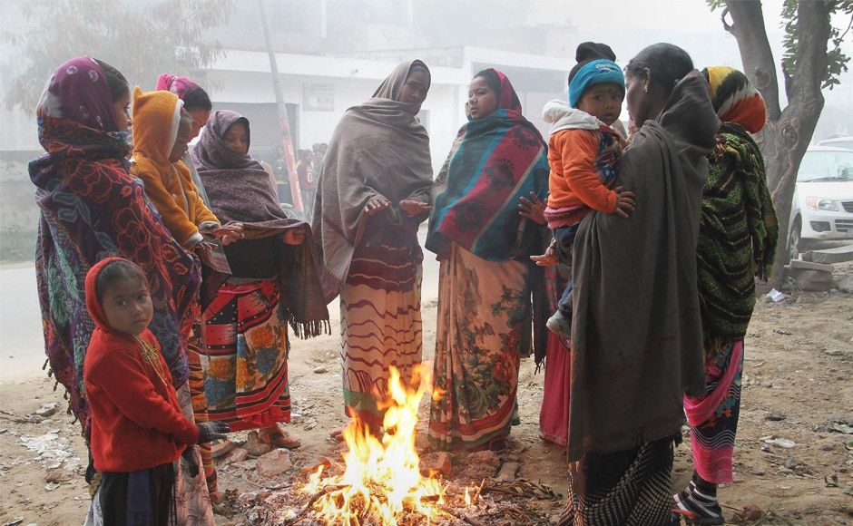 Women warm themselves near a fire during cold and fog morning in Jammu in Jammu and Kashmir on Wednesday. PTI