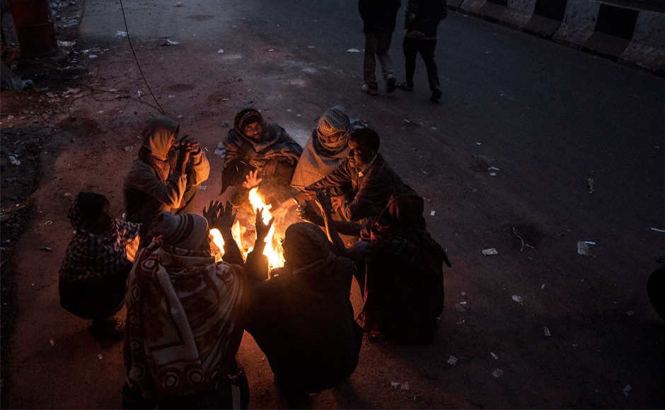 People sit around a fire to warm themselves during cold winter morning in New Delhi. On Thursday, low visibility due to thick fog led to train and flight services being cancelled in the national capital. PTI