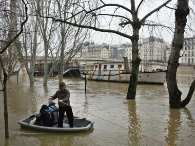 People use a dinghy boat to reach a barge on the river Seine in Paris. AP