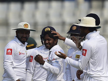 Sri Lankan cricketers congratulate teammate Akila Dananjaya (C) after the dismissal of the Bangladesh cricket captain Mahmudullah Riyad during the second day of the second cricket Test between Bangladesh and Sri Lanka at the Sher-e-Bangla national cricket stadium in Dhaka on February 9, 2018. / AFP PHOTO / Munir UZ ZAMAN