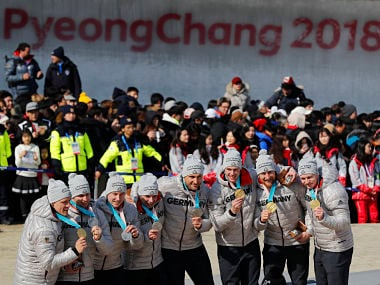 The two German teams celebrate during the medal ceremony after the four-man bobsled competition final at the 2018 Winter Olympics in Pyeongchang, South Korea, Sunday, Feb. 25, 2018. Driver Francesco Friedrich, Candy Bauer, Martin Grothkopp and Thorsten Margis of Germany won the gold and driver Nico Walther, Kevin Kuske, Alexander Roediger and Eric Franke of Germany tied with Korea for silver. (AP Photo/Andy Wong)