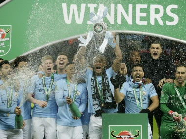 Manchester City's Vincent Kompany (C) lifts the League Cup after City defeated Arsenal in the final 3-0, at Wembley stadium in London. AP
