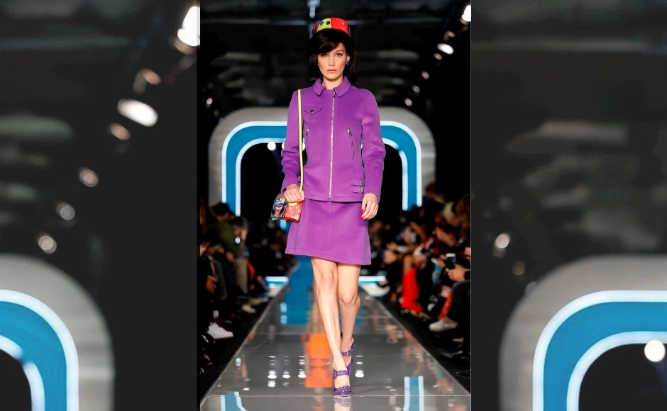 Creations featured oranges, purples, and yellows. 62 looks were presented that recreated the late First Lady's iconic tweed skirt suit and pillbox hat. Bella Hadid walks the ramp for Moschino. Image from Twitter/@_daintyrose_