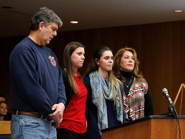 Madison Rae Margraves and her sister Lauren stand with their parents after giving their victim statements during the sentencing hearing for Larry Nassar, a former team USA Gymnastics doctor who pleaded guilty in November 2017 to sexual assault charges, in the Eaton County Court in Charlotte, Michigan, U.S., February 2, 2018. REUTERS/Rebecca Cook - RC170A4985E0