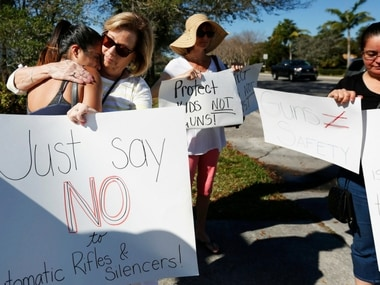 Cathy Kuhns, right, hugs Ana Paula Lopez, left, as they stands on a street corner holding up anti gun signs in Parkland, Fla., on Saturday, Feb. 17, 2018. As families begin burying their dead, authorities are questioning whether they could have prevented the attack at the high school where a gunman, Nikolas Cruz, took several lives. AP