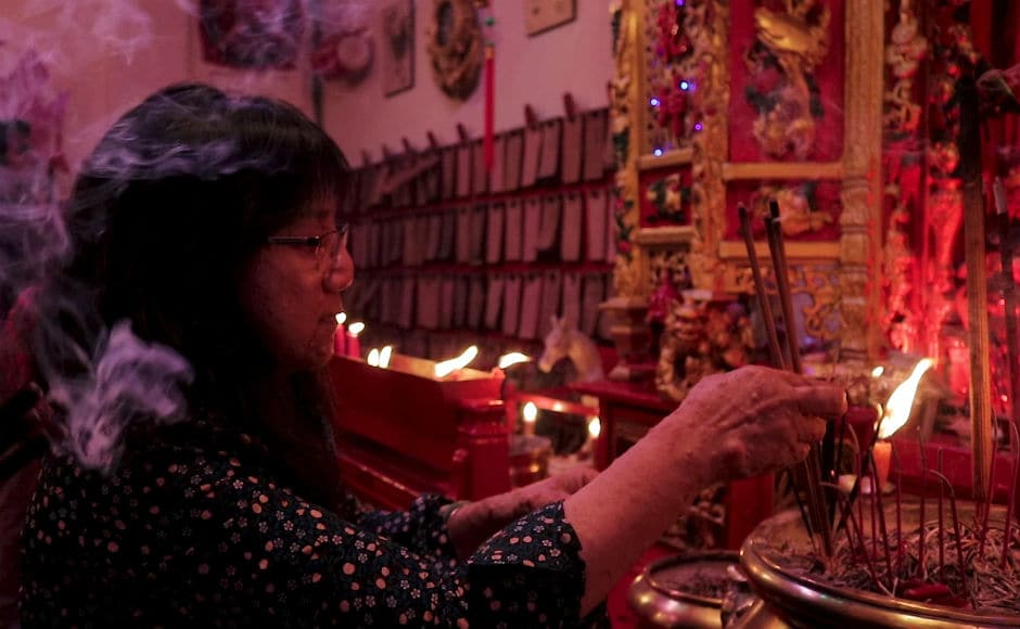 Hundreds of people gathered at the temple on Thursday. They burned incense and prayed to the warrior god Kwan Kung. Firstpost/Sonali Jain