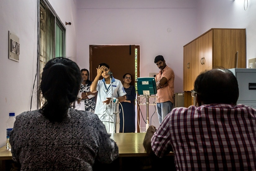 "A subject, sharing a stressful situation she made up. She is participating in an experiment conducted by Krishnaveni (standing behind her) that will help ascertain ""the role of psychological stress in the development of adult chronic diseases."""