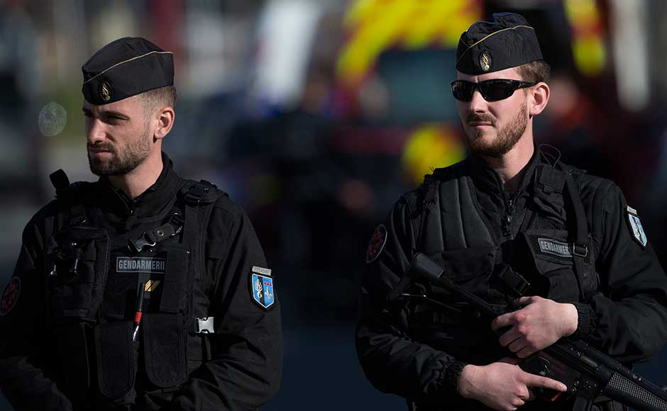Named as Redouane Lakdim and said by security sources to have Moroccan nationality, the gunman first hijacked a car in Carcassonne, killing a passenger and injuring the driver, before shooting and injuring a policeman who was out jogging. French Police officers cordon off the area during an incident in Trebes. AP