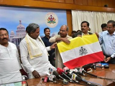 Chief minister Siddaramaiah unveiling the new flag of Karnataka. Twitter @CMofKarnataka