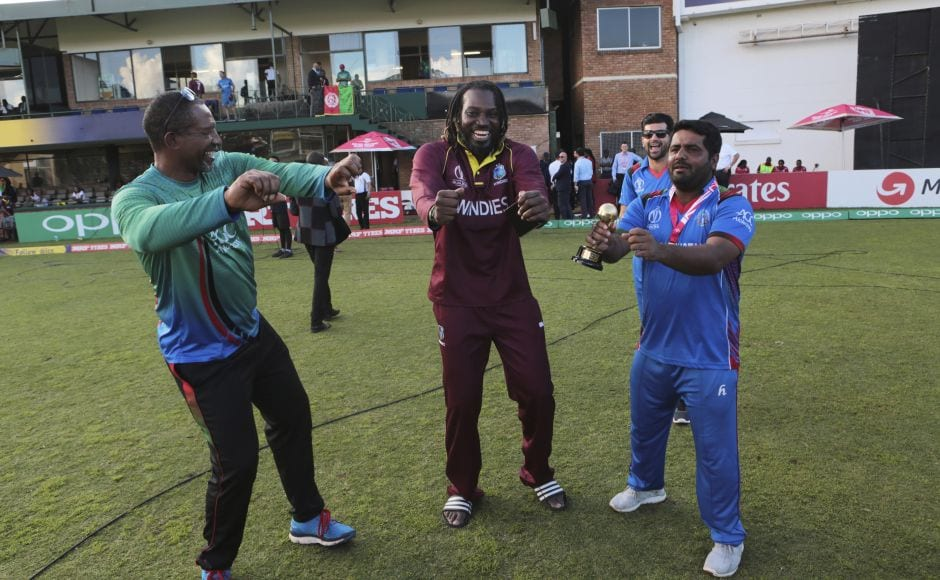 West Indies player Christopher Gayle, centre, dances with Afghanistan batsman Mohammad Shahzad, right, and Afghanistan coach Phill Simmons after their cricket world cup qualifier match at Harare. AP