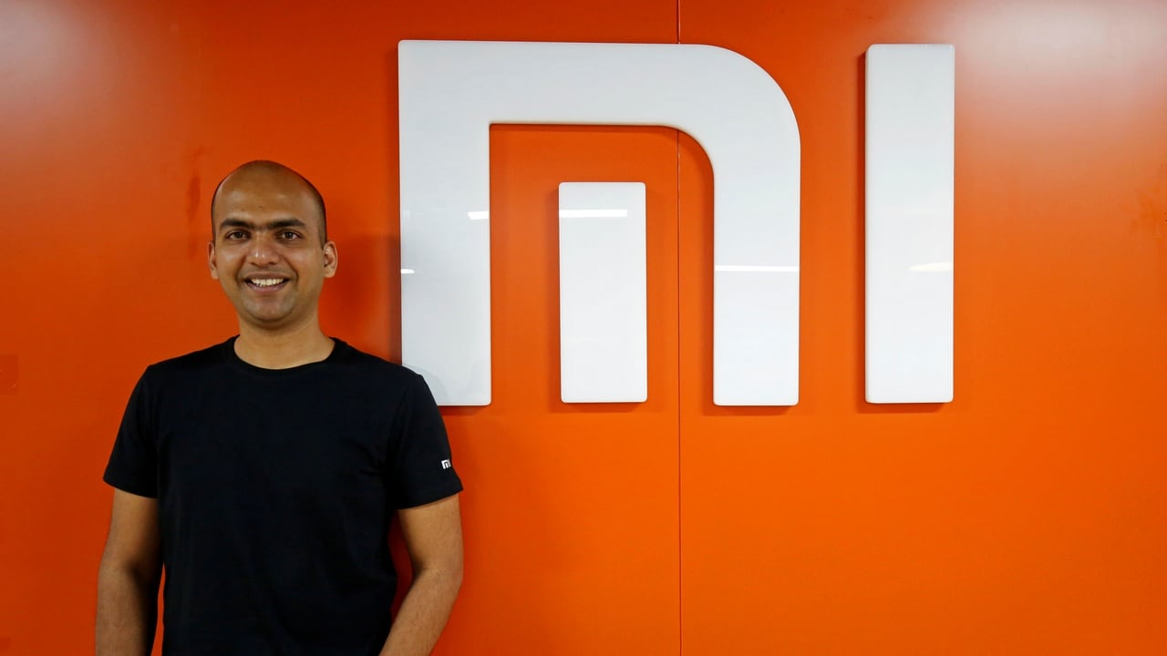 Manu Kumar Jain, Managing Director of Xiaomi India, poses next to the logo of Xiaomi after an interview with Reuters inside his office in Bengaluru, India, January 18, 2018. Picture taken January 18, 2018. REUTERS/Abhishek N. Chinnappa - RC1AEA1E1530