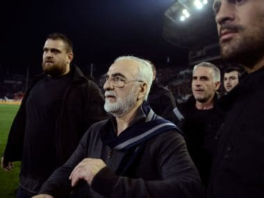 File photo of PAOK owner, businessman Ivan Savvidis, center, walking on the pitch escorted by his bodyguards. AP