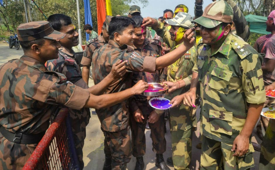 BSF soldiers exchanged sweets and gulal with thier Bangladeshi counterparts on the occasion of Holi at Akhaura border near Agartala in Tripura. The celebration of the festival started on Thursday evening with Holika dahan. PTI