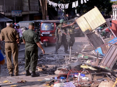 Sri Lanka's army soldiers remove the debris of a vandalised building in Digana, a suburb of Kandy. AP
