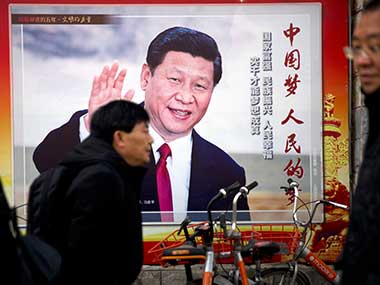 People walk past a billboard showing Chinese President Xi Jinping along a street in Beijing. AP